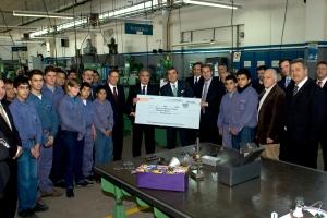 Directivos de Mercedes-Benz y Banco Galicia haciendo entrega del cheque a_ la escuela tecnica Fundacion Fangio